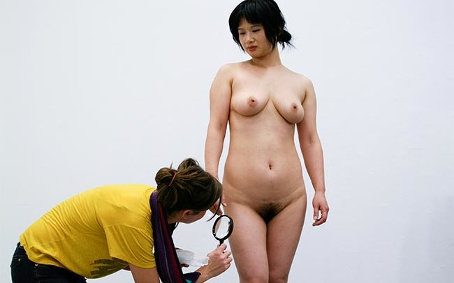 An audience uses a magnifier to examine Chun Hua Catherine Dong's body