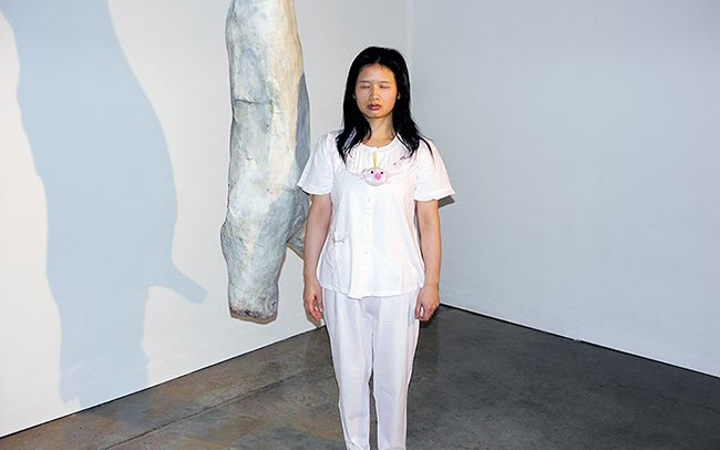 Chun Hua Catherine Dong wears pyjama and walks around in a gallery, posting herself beside art objects with her eyes close