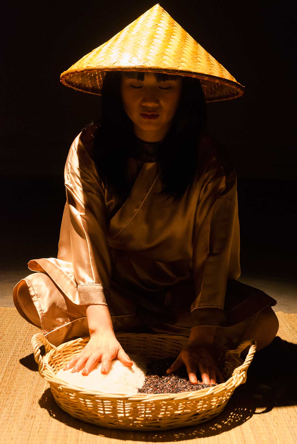 Chun Hua Catherine Dong closes her eyes, sits on a mat and gently touches the black and white rice in front of her, she is ready to perform her rice performance