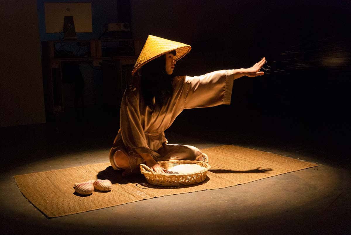 Chun Hua Catherine Dong grabs a handful rice and throws it to audiences, the audiences can feel the gentle touch of the rice, the rice connects her and her audience