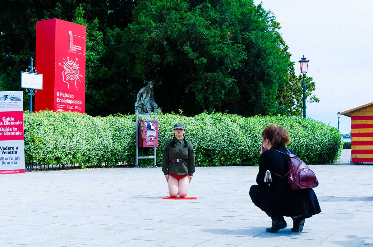 Chun Hua Catherine Dong wear a military suit and red underwear, kneeling on a washboard and keeping straight and still as long as she can in Venice Biennale in 2013