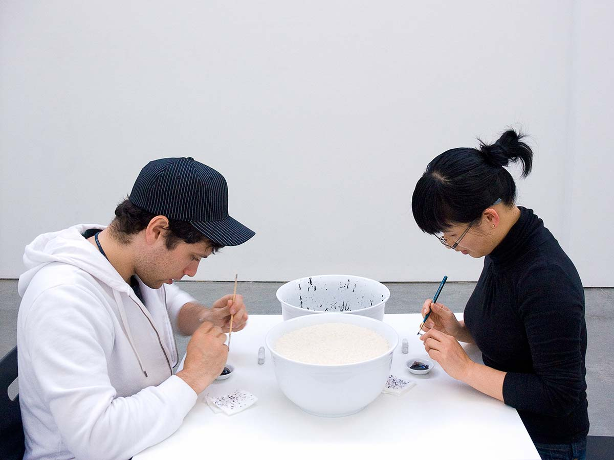Chun Hua Catherine Dong paints rice with black ink one after one and invites audiences to sit in front of her and paint the rice with her