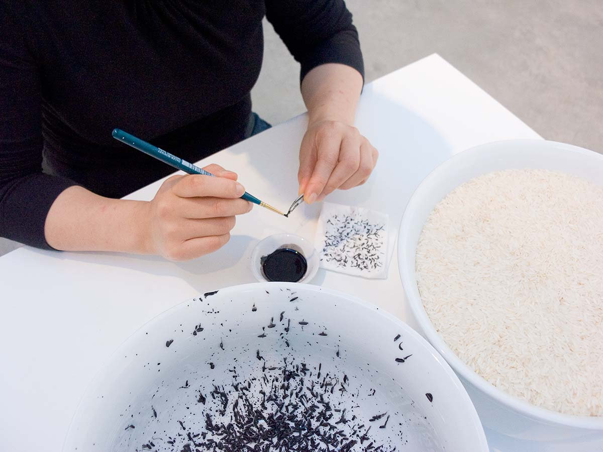 Chun Hua Catherine Dong paints rice with black ink in her performance in Vancouver, she wants amount of rice in two bowls are equal