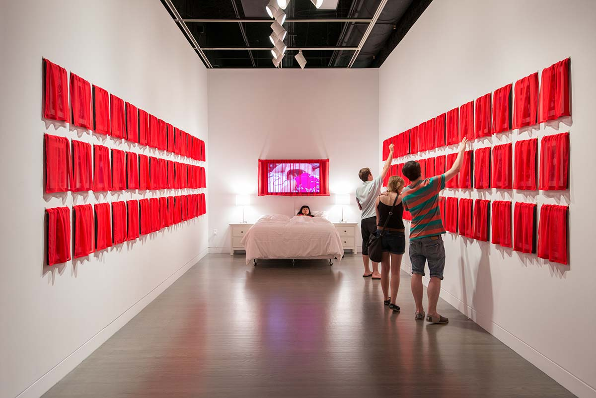 Chun Hua Catherine Dong's work, Husbands and I installation, at Leonard & Bina Ellen Art Gallery in 2012. Chun Hua Catherine Dong covered all of her photographs with red fabric, viewers has to lift up the curtains and see the photographs