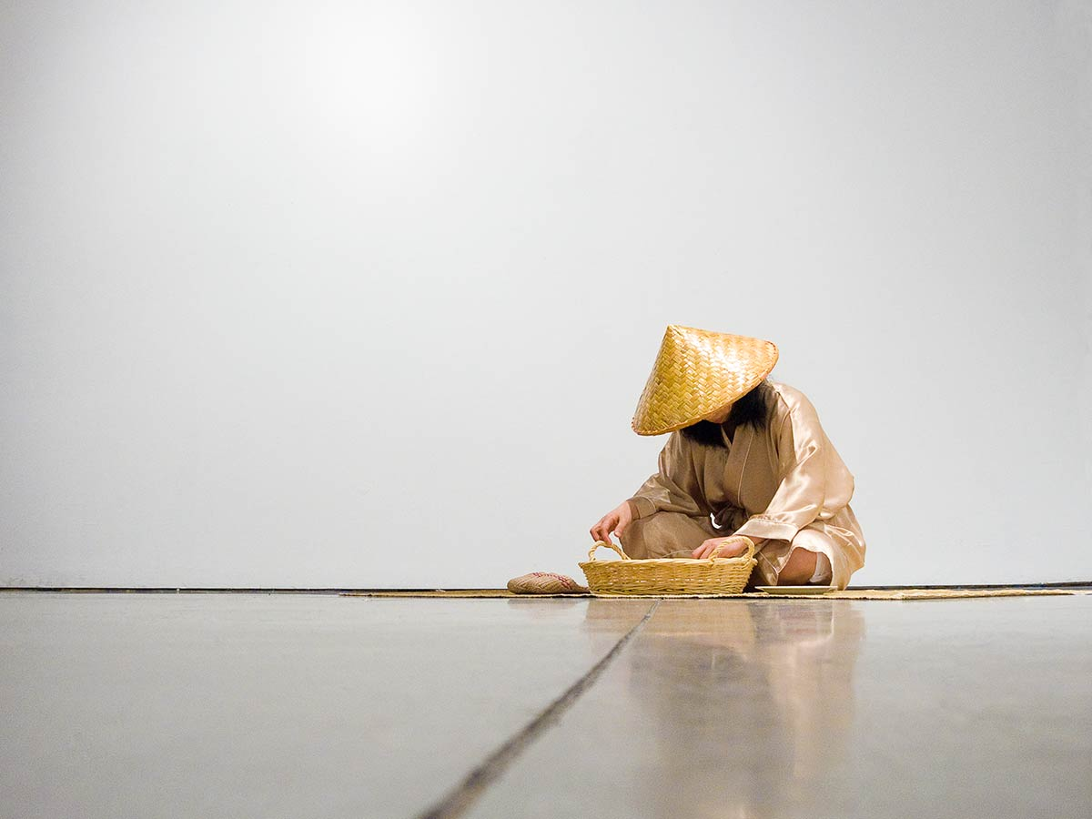 Chun Hua Catherine Dong sits on a bamboo mat and picks rice one after one as a meditation, it is infinite task