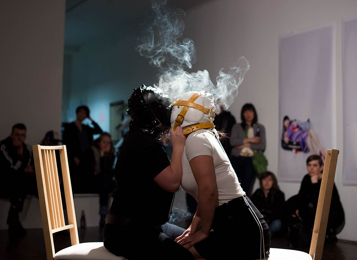 Chun Hua Catherine Dong performs at Articule Montreal: two females wear masks and kiss each other with smoke on their heads