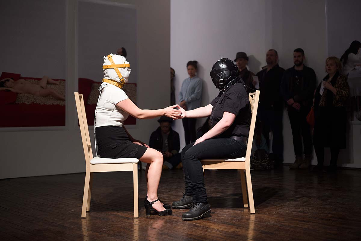 Chun Hua Catherine Dong performs at Articule Montreal: two females wear masks and touch each others