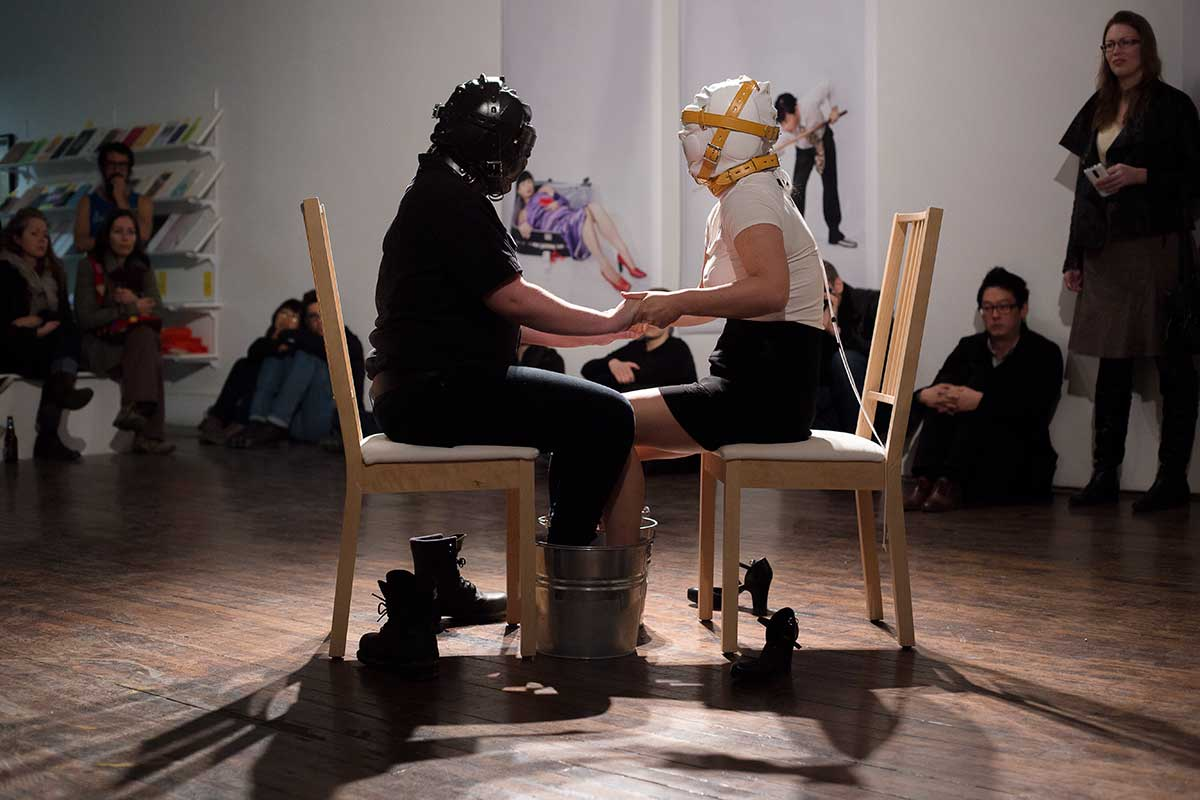 Chun Hua Catherine Dong performs at Articule Montreal: two girls wear masks and put their feet on two buckets, which one is filled with ice, another one is filled with boiled water