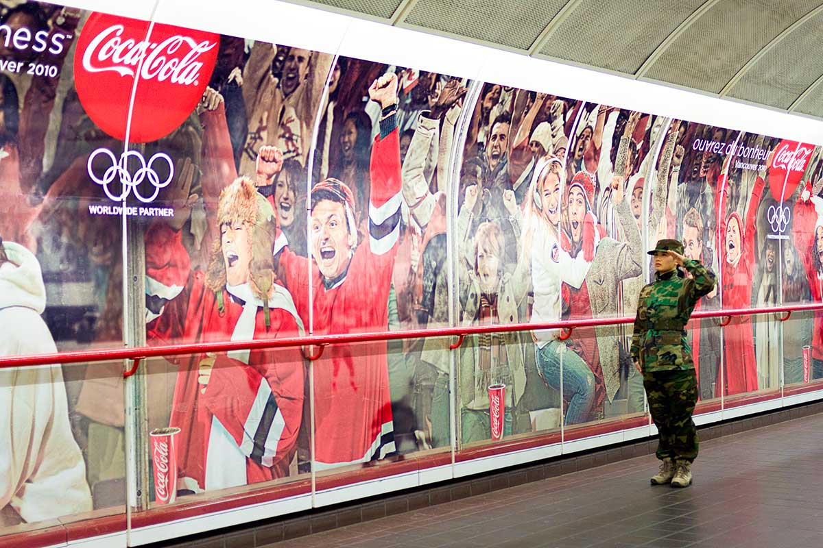 Chun Hua Catherine Dong wears military suit and salutes with her left hand, a wrong hand, to Olympic advertisement during Vancouver 2010 Winter Olympics