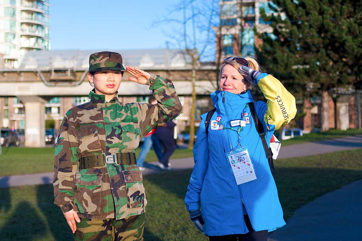 Chun Hua Catherine Dong wears military suit and salutes with her left hand, a wrong hand, to Olympic symbols. she invites people to salute with her