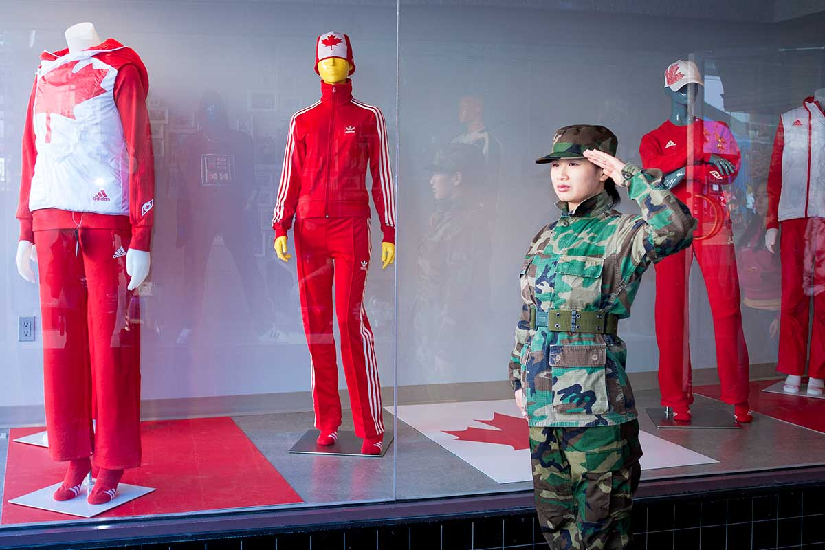 Chun Hua Catherine Dong wears military suit and salutes with her left hand, a wrong hand, to Olympic symbols during Vancouver 2010 Winter Olympics