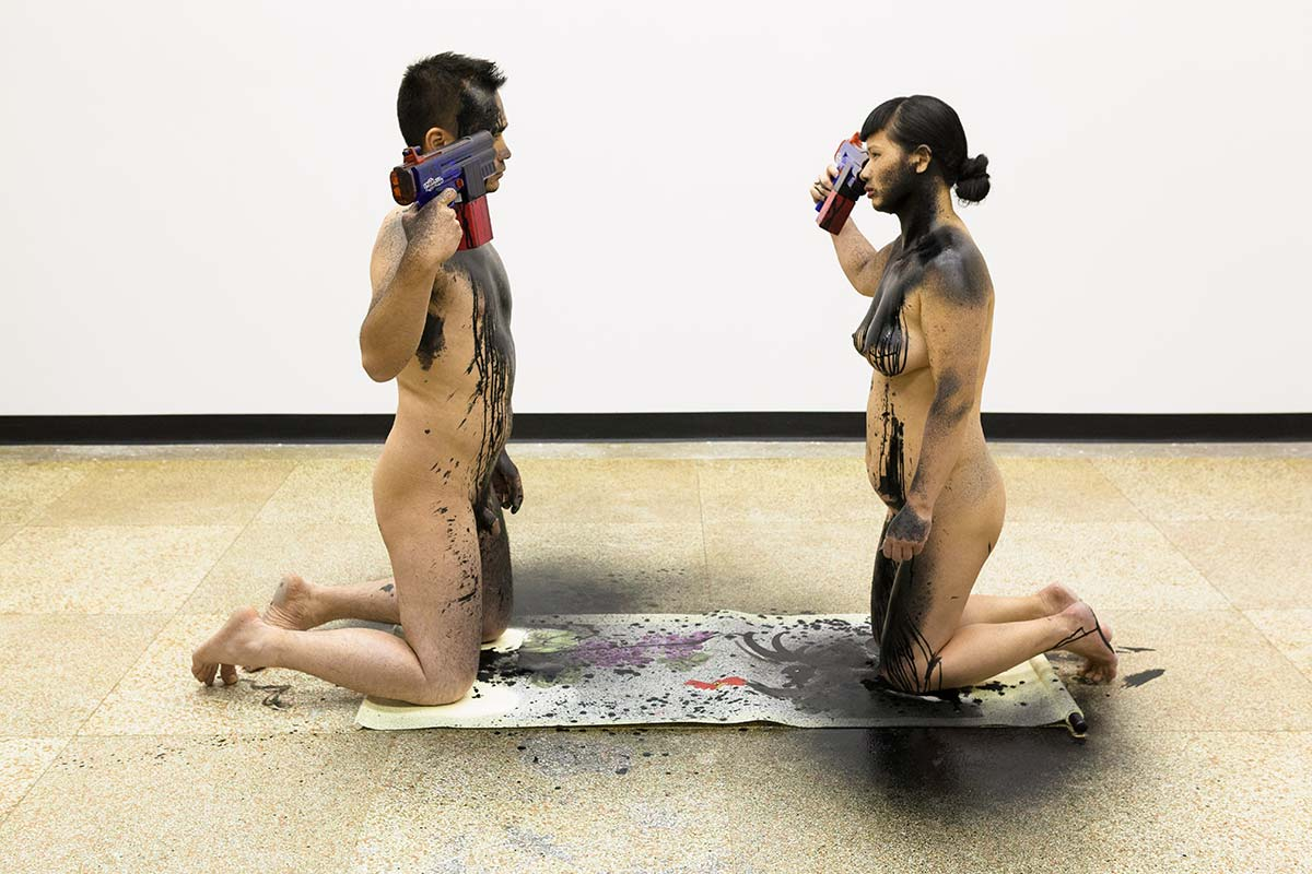 Chun Hua Catherine Dong and her performance partner are naked, kneeing on a Chinese traditional painting, they shoot themselves with ink