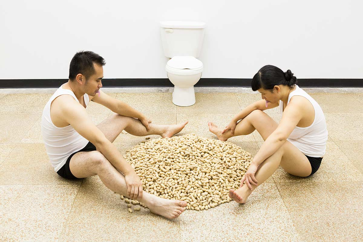 Chun Hua Catherine Dong and her performance partner sit in front of a toilet and look at a big pile of peanuts