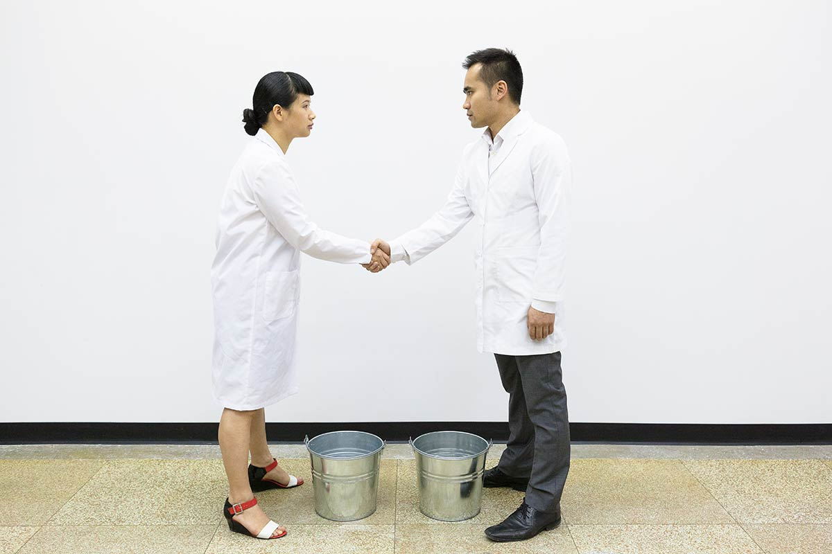 Chun Hua Catherine Dong and her performance partner wear lab coats, shaking hands n front of two buckets