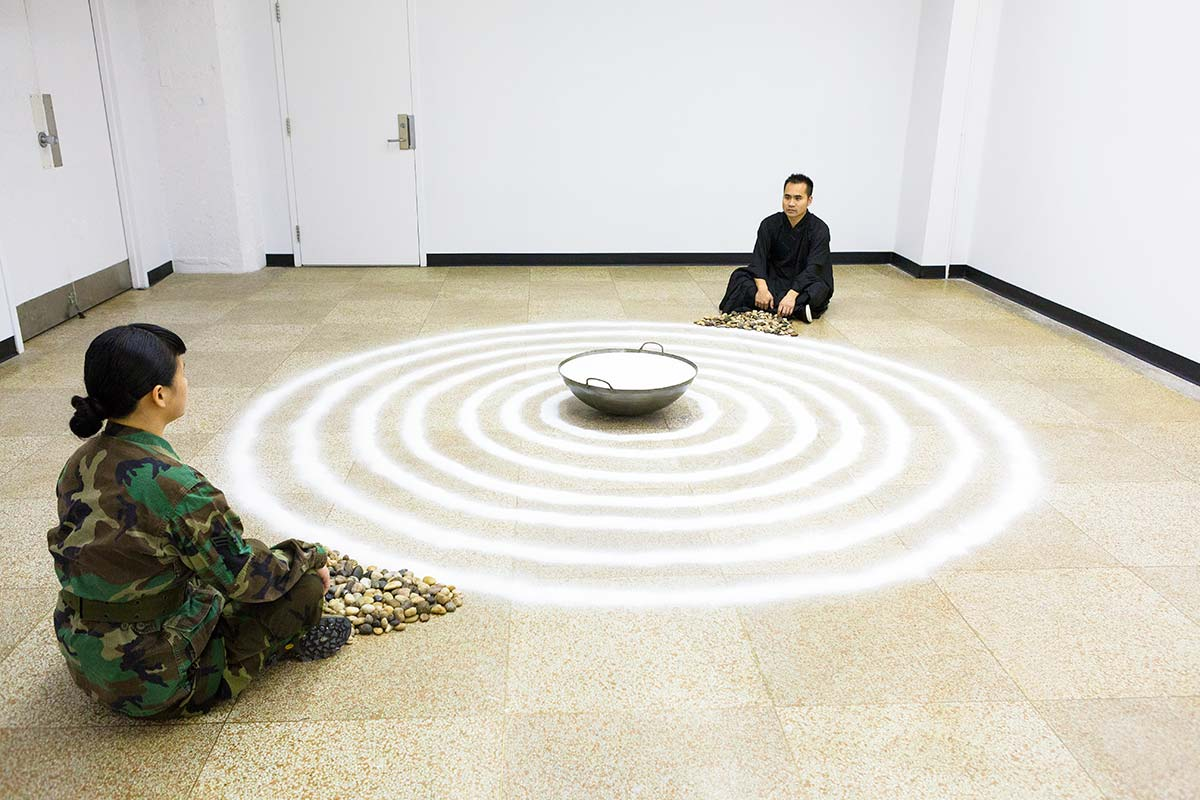 Chun Hua Catherine Dong and a monk meditate in front of seven circles that was made with salt