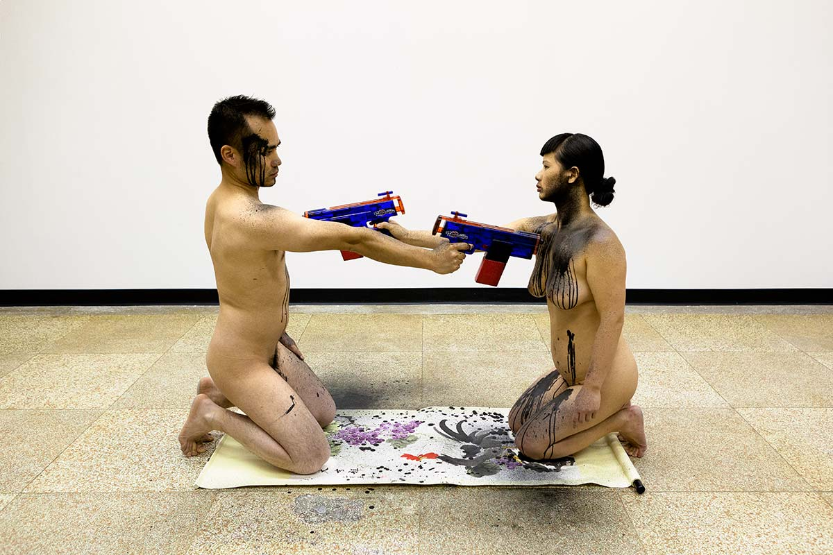 Chun Hua Catherine Dong and her performance partner are naked, kneeing on a Chinese traditional painting, they shoot each other's hearts with ink