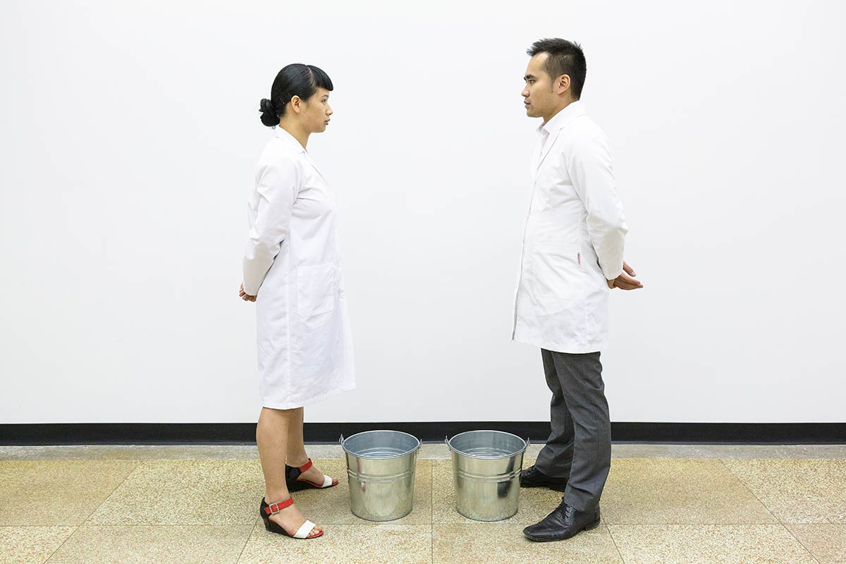 Chun Hua Catherine Dong and her performance partner wear lab coats, standing in front of two buckets and looking at each other