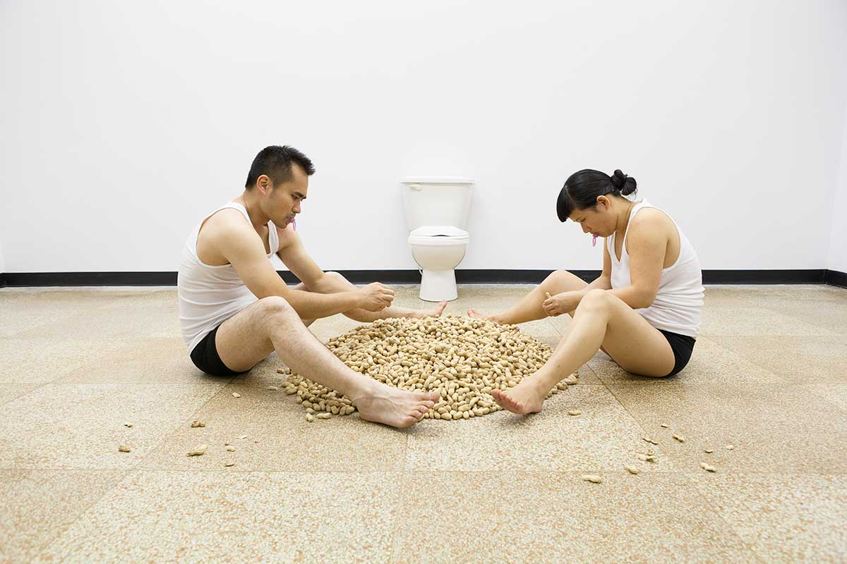 Chun Hua Catherine Dong and her performance partner are shucking peanuts, they throw peanut shells on floor and store peanut seeds in their underwear