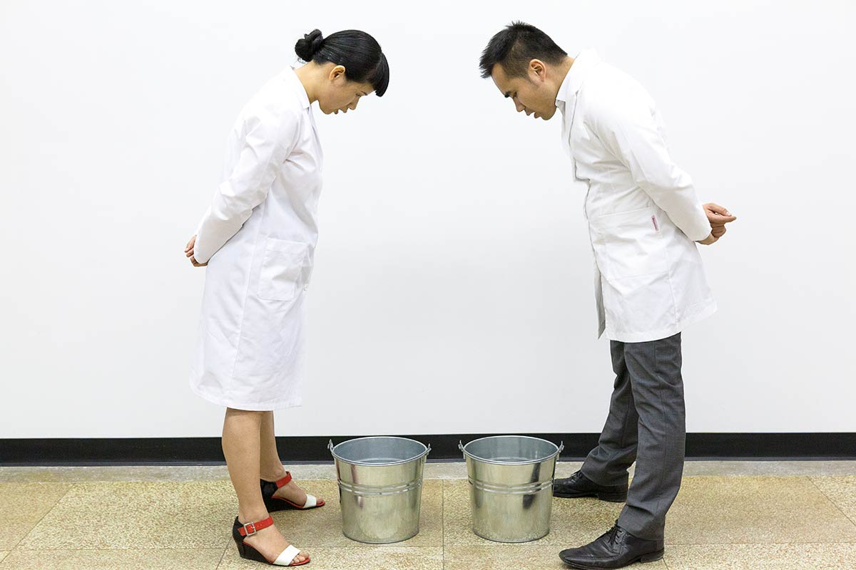 Chun Hua Catherine Dong and her performance partner wear lab coats, bowing to each other, opening their mouths and letting their saliva dropping into buckets