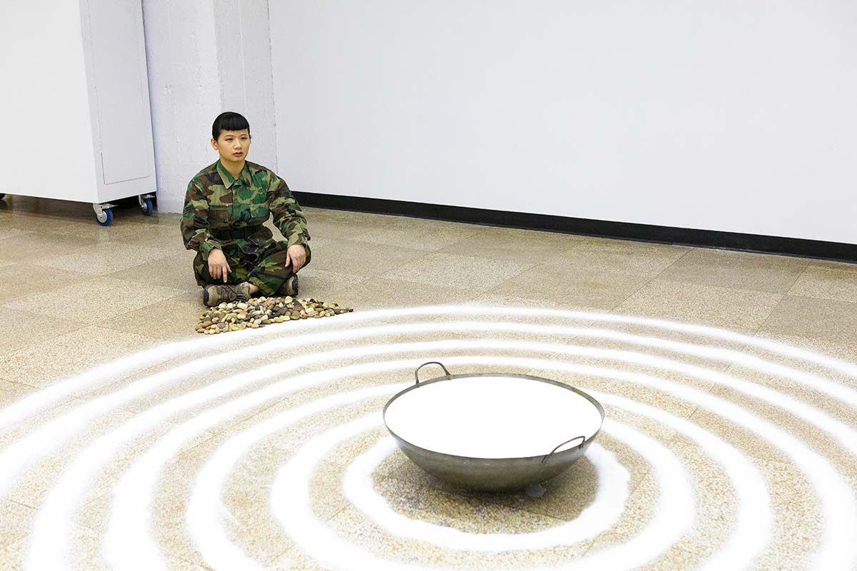 Chun Hua Catherine Dong is a soldier and she is meditating in front of salt and milk