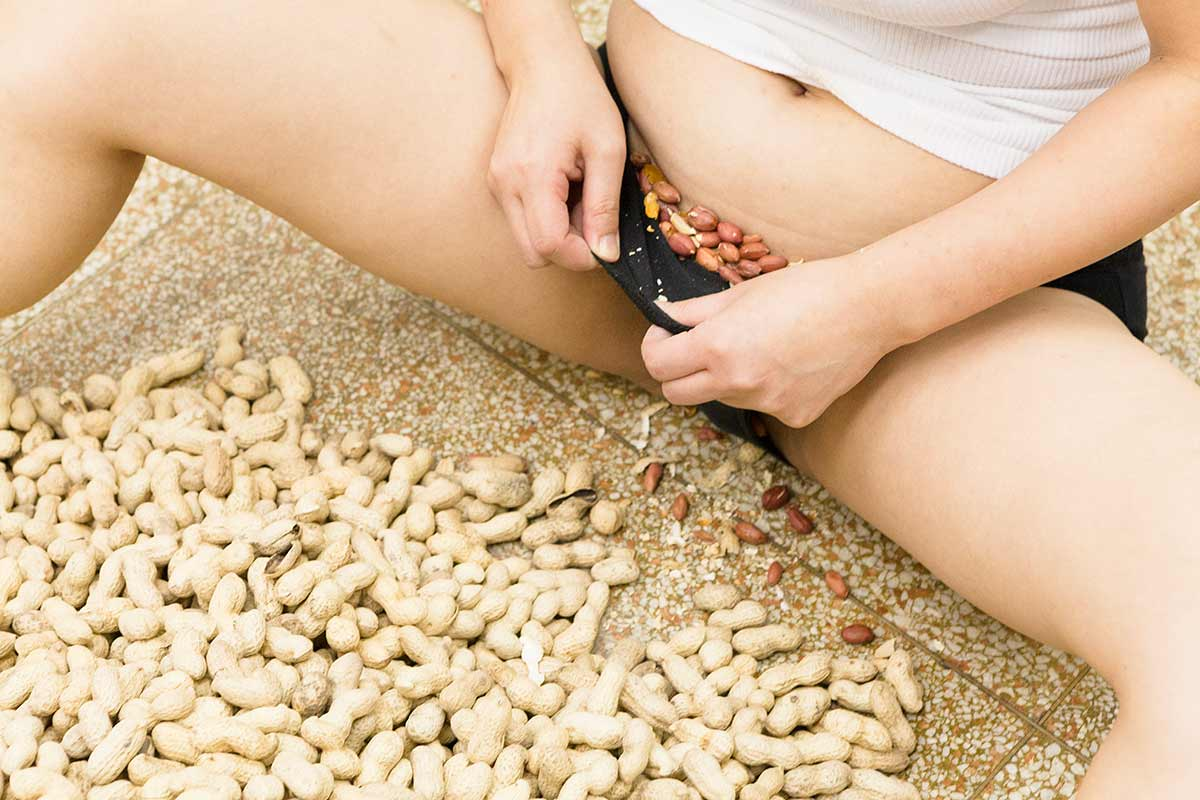 Chun Hua Catherine Dong is shucking peanuts and storing peanut seeds in her underwear