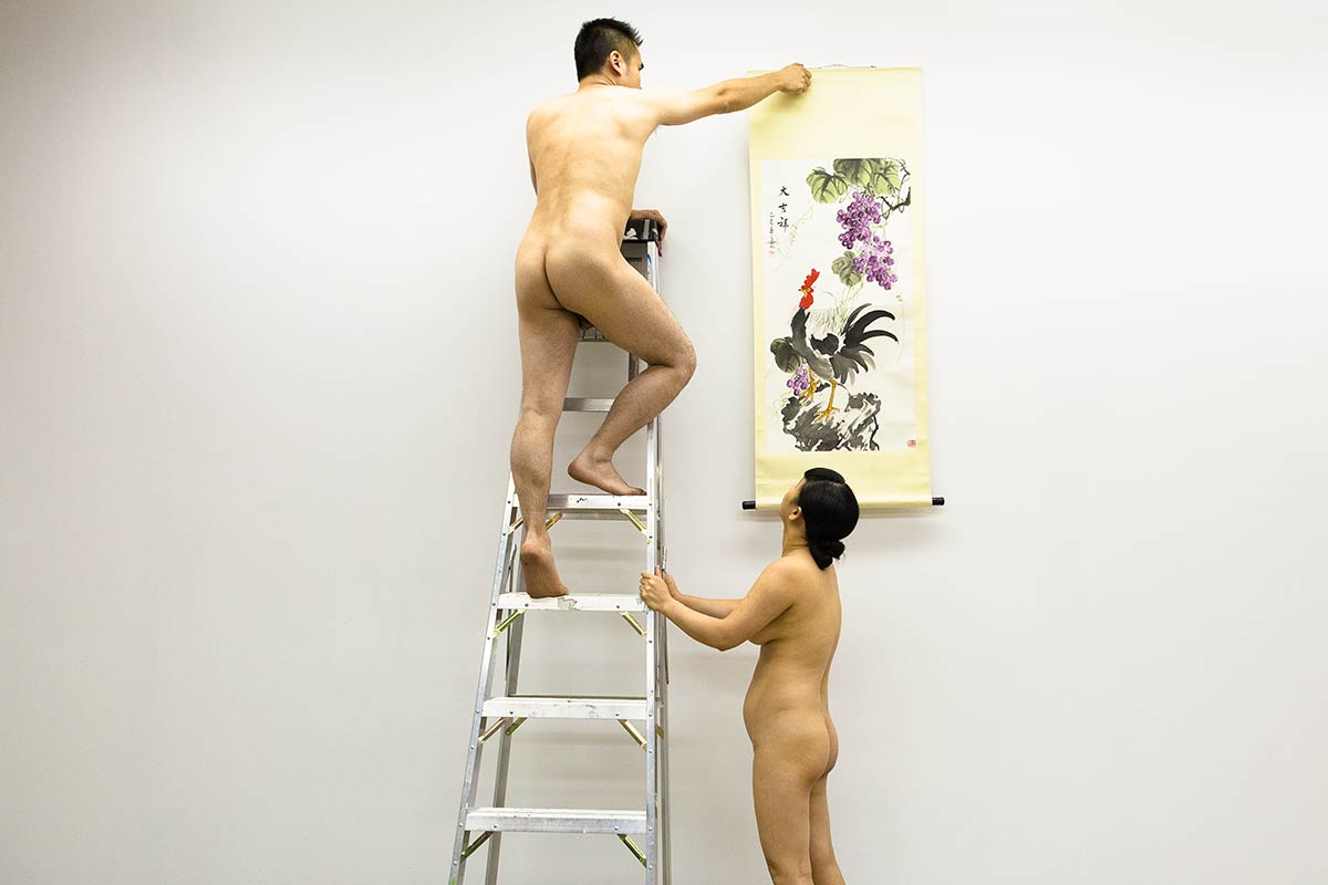 Chun Hua Catherine Dong is watching her performance partner to take down a Chinese traditional painting, they are naked