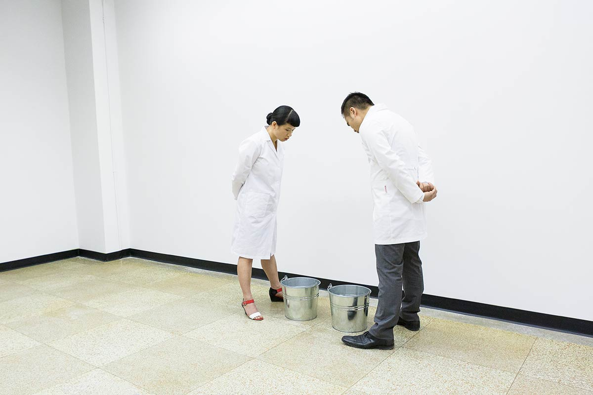 Chun Hua Catherine Dong and her performance partner wear lab coats and drop their saliva to buckets