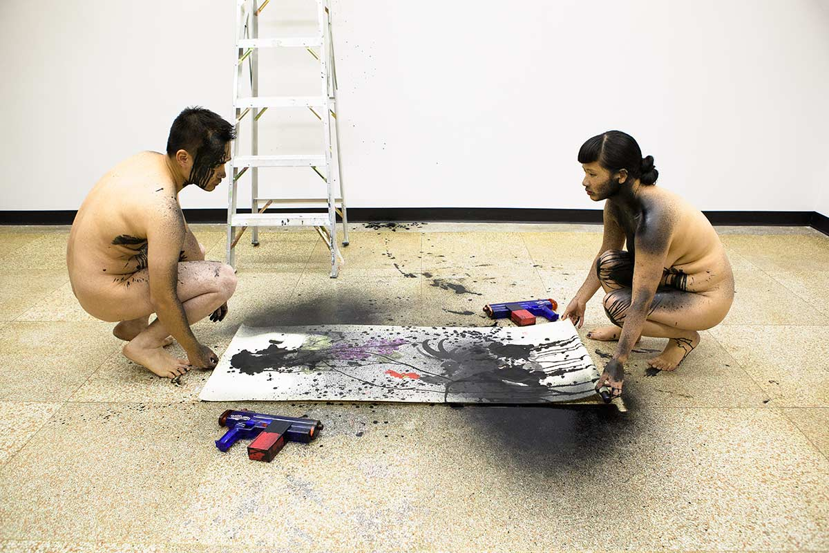 Chun Hua Catherine Dong and her performance partner are naked, lifting a Chinese traditional painting where they kneed on