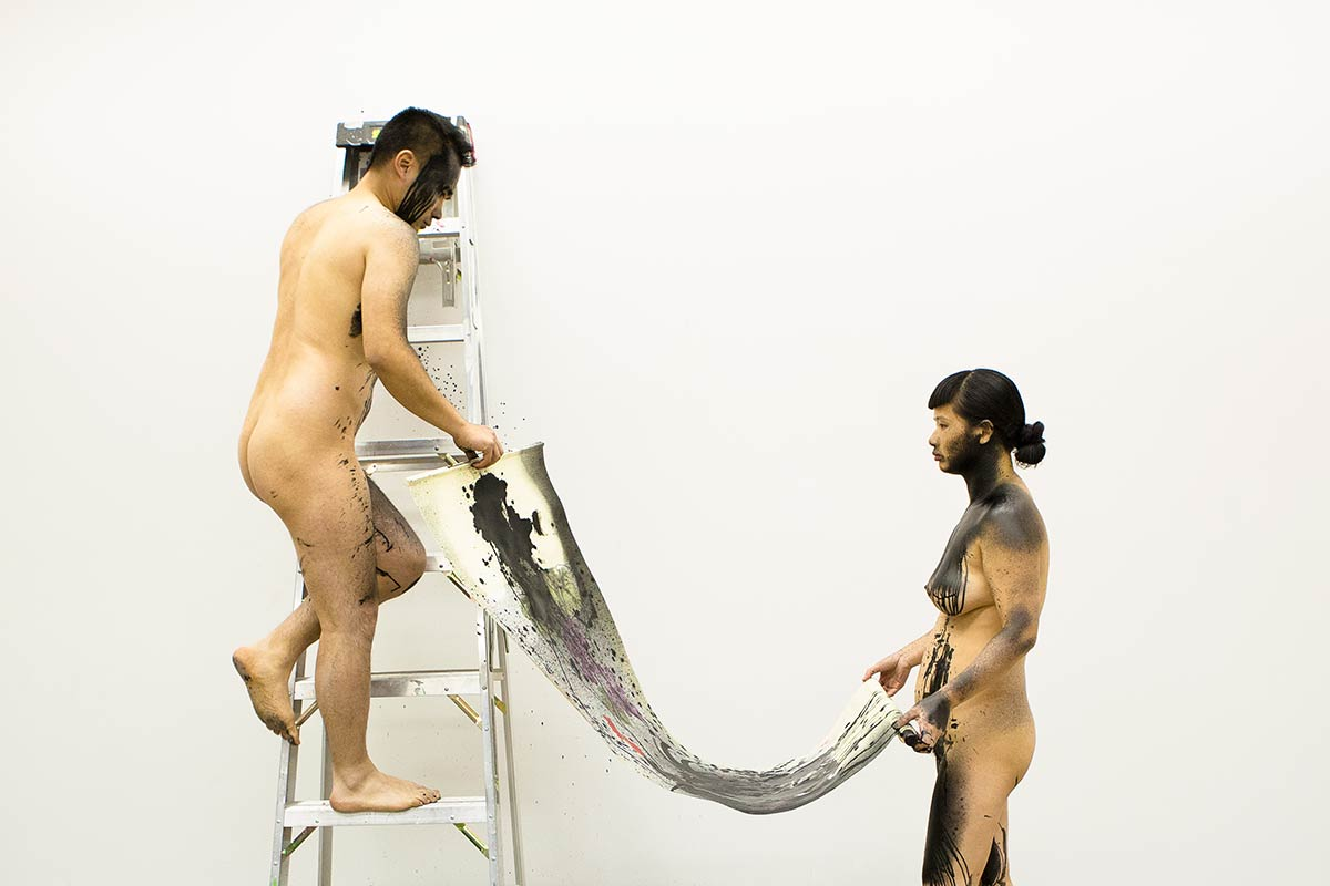 Chun Hua Catherine Dong is naked, helping her performance partner to hang a  Chinese traditional painting on a wall