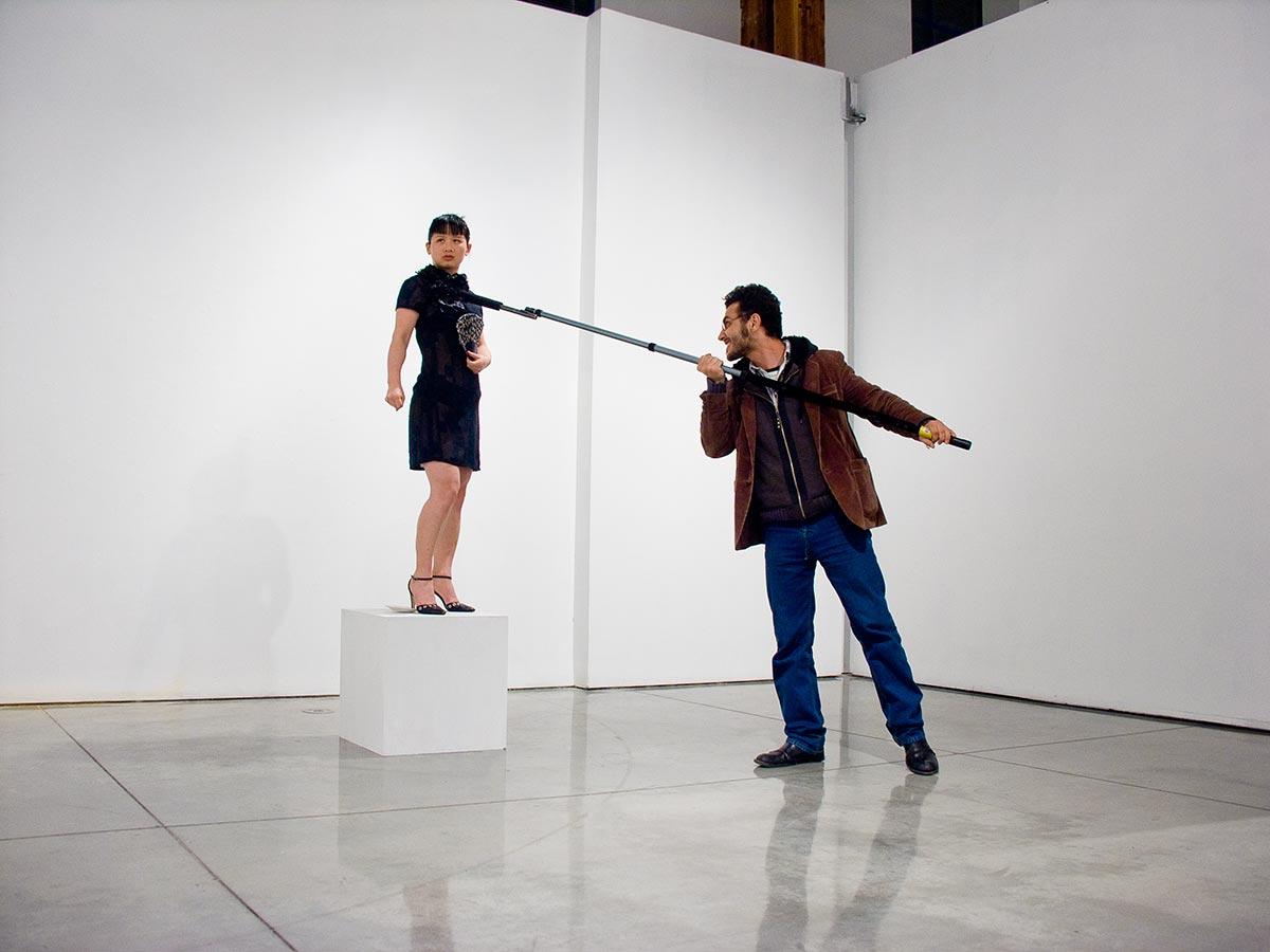 Chun Hua Catherine Dong stands on a plinth and holds her fist,  when the viewers use a boom microphone to inspect my body, sharp sounds will occur