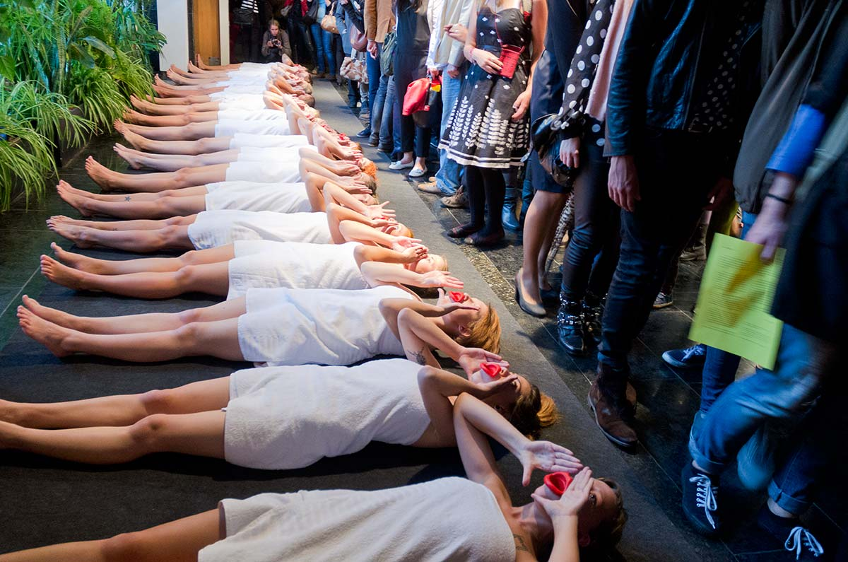 Chun Hua Catherine Dong's performance at Kaunas Biennial: nineteen girls wear red mouthpieces and white bath towels, standing in a row, repeating  three still gestures: standing, kneeing, and lying on the floor.