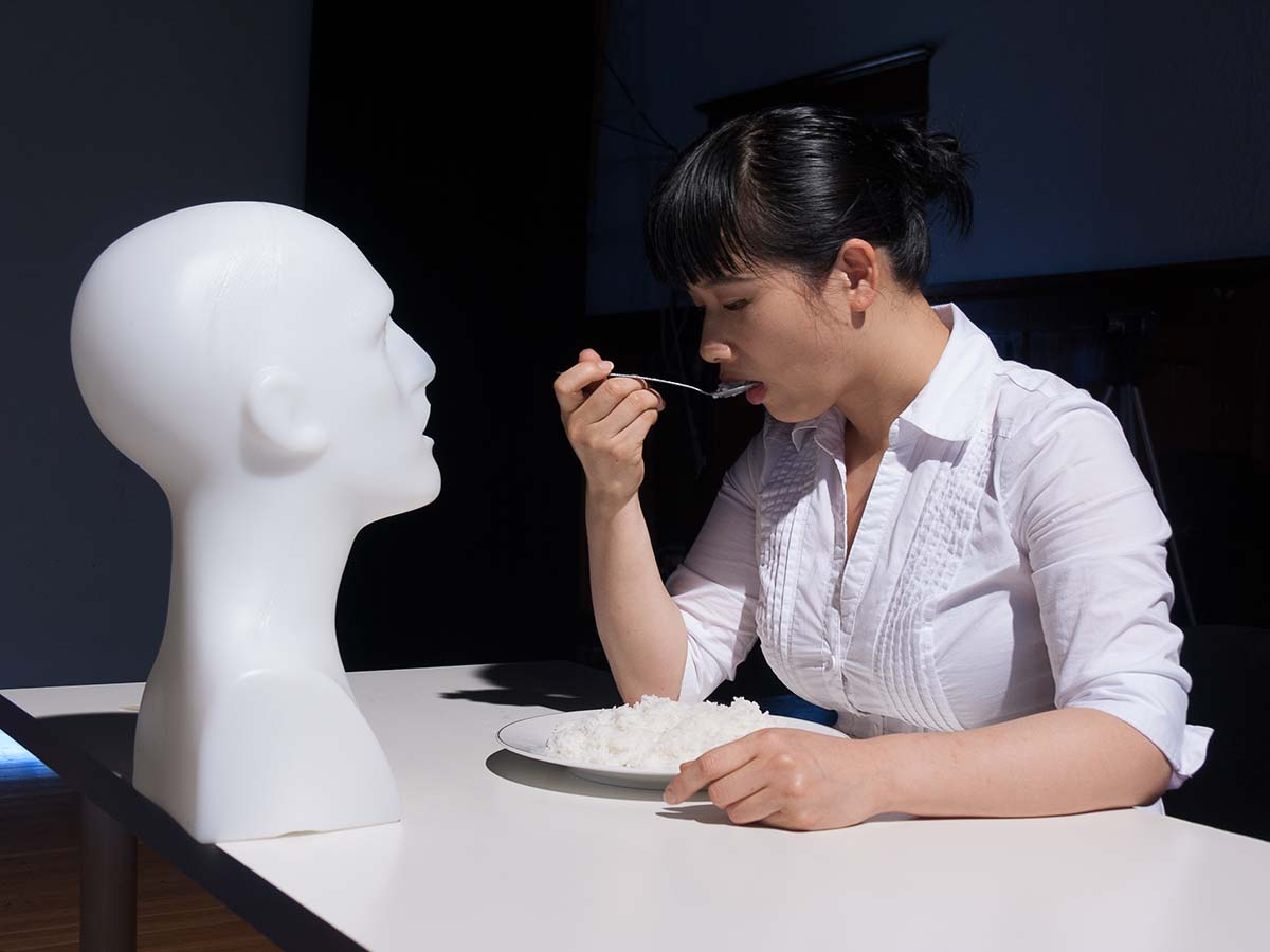 Chun Hua Catherine Dong chews up rice, splits it on a spoon and feed a male mannequin head at Western Front Vancouver