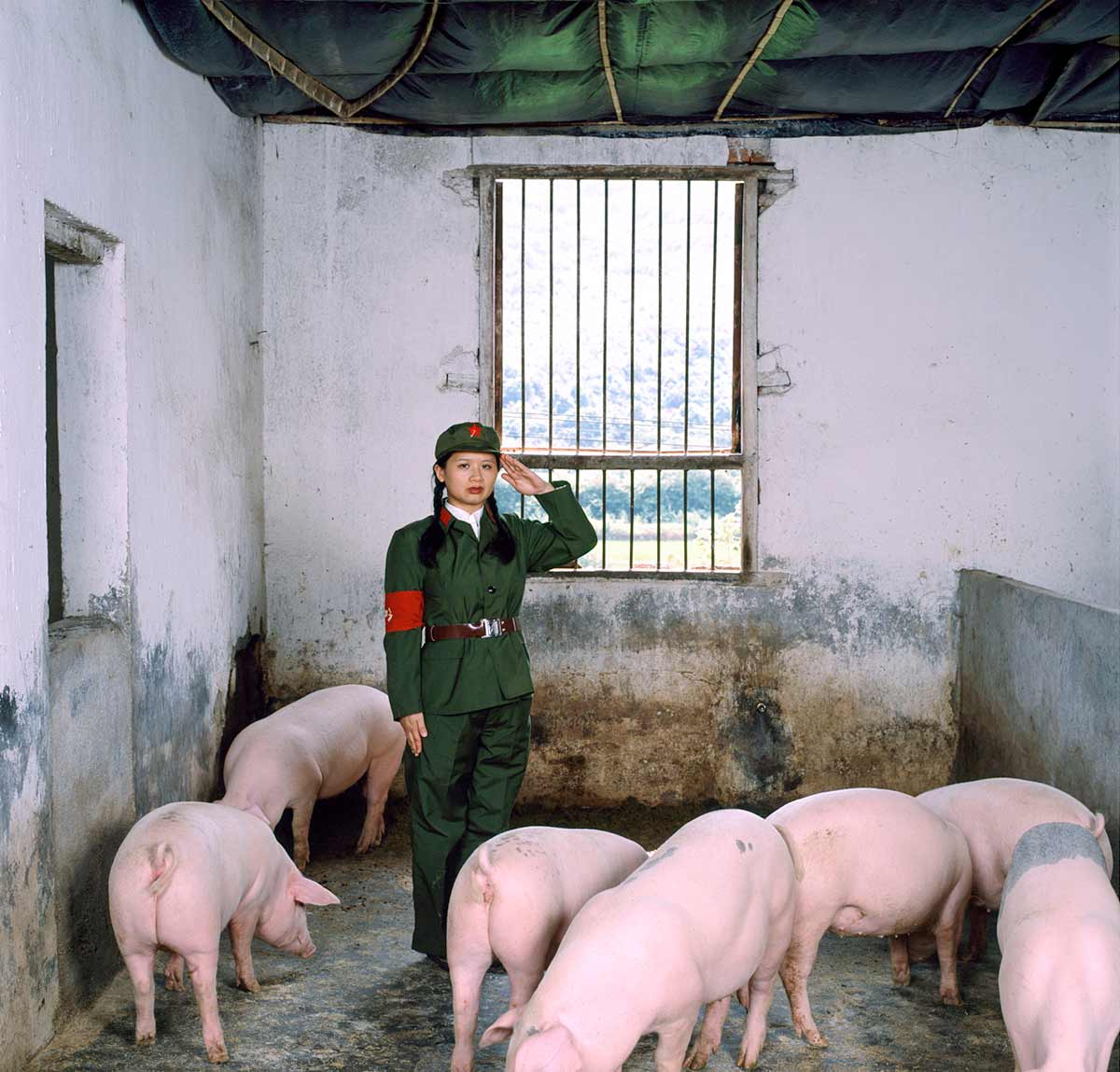 Chun Hua Catherine Dong performs the Red Guard in the Chinese Cultural Revolution. she salutes with her left hand in a pig house