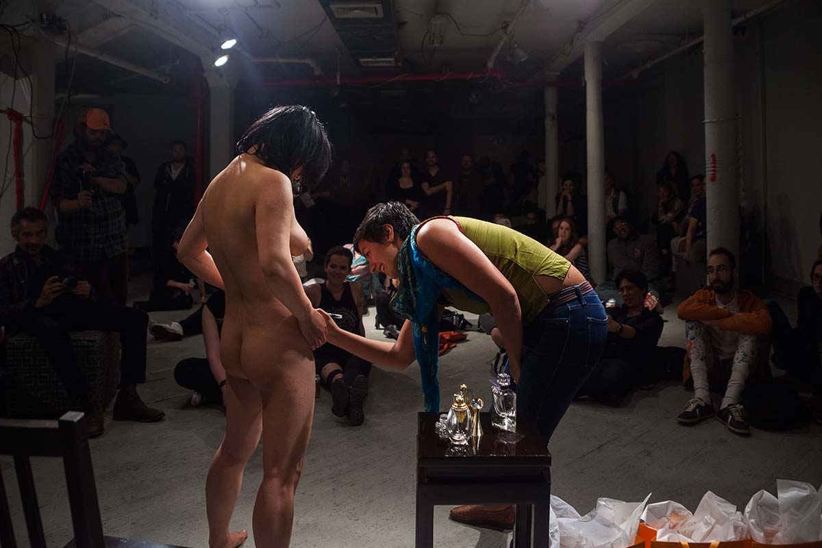 a woman who brought Chun Hua Catherine Dong for a night is writing her name on Dong's perfumed body