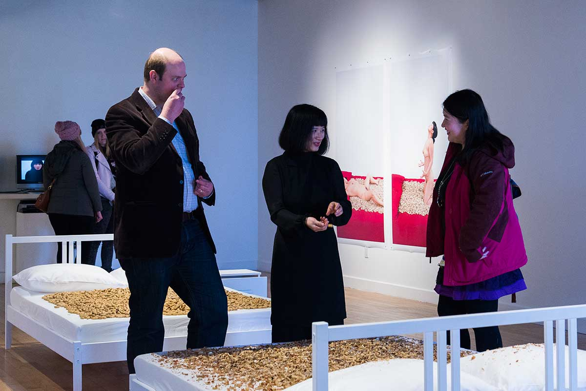 Chun Hua Catherine Dong shucks peanuts and leave peanuts' shell on an empty bed, she also invites audiences to shuck peanuts with her