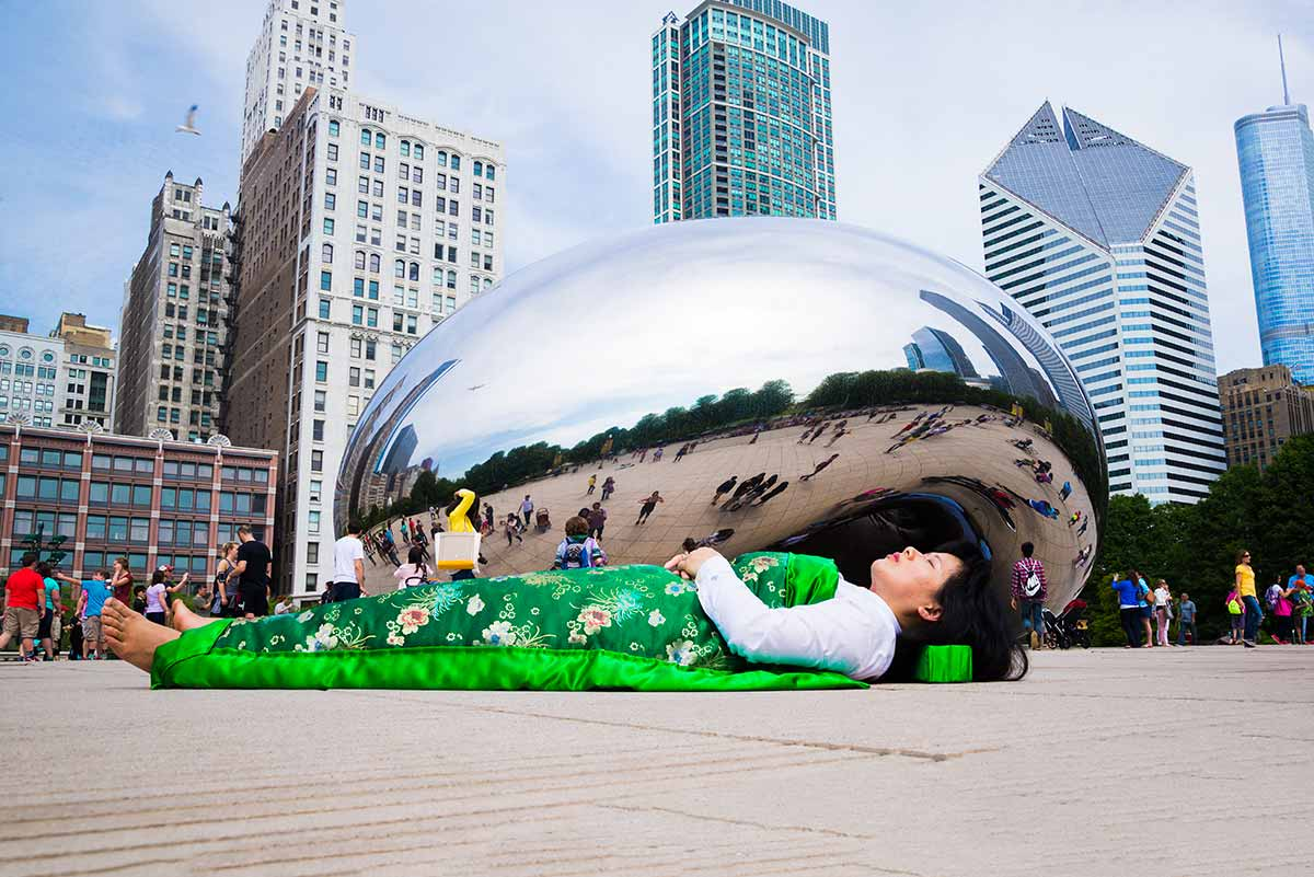 each time Chun Hua Catherine Dong travels to a city, she takes photographs of herself lying in front of historical and tourist sites, covered by a silk corpse sheet