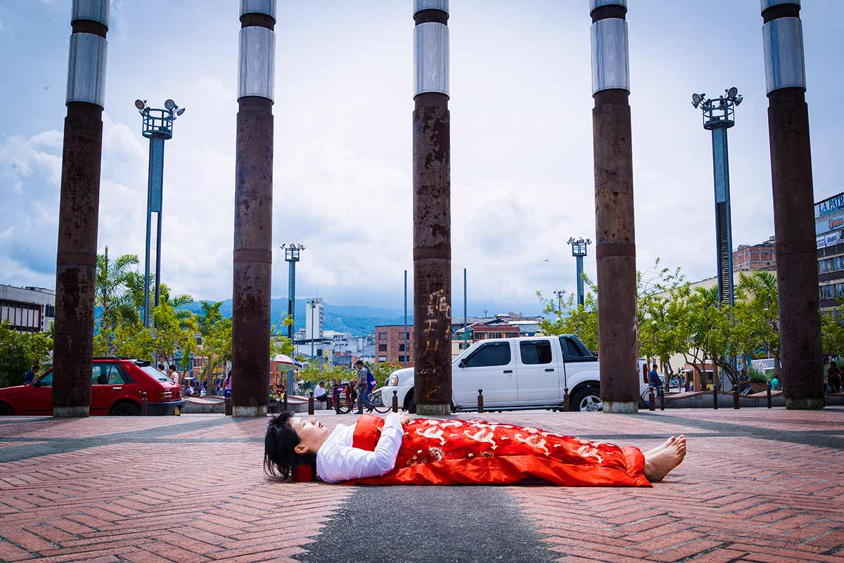 each time Chun Hua Catherine Dong travels to a city, she makes a new silk duvet cover, and takes photographs of herself lying in front of historical and tourist sites, covered by the duvet