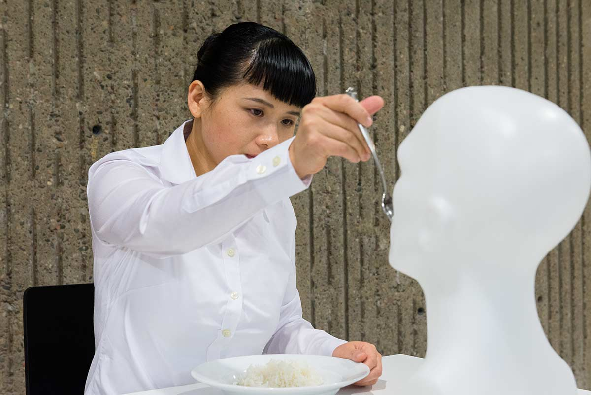 Chun Hua Catherine Dong feeds pre-masticated rice to a white male mannequin head for four hours at Nuit Blanche in Montreal in 2014