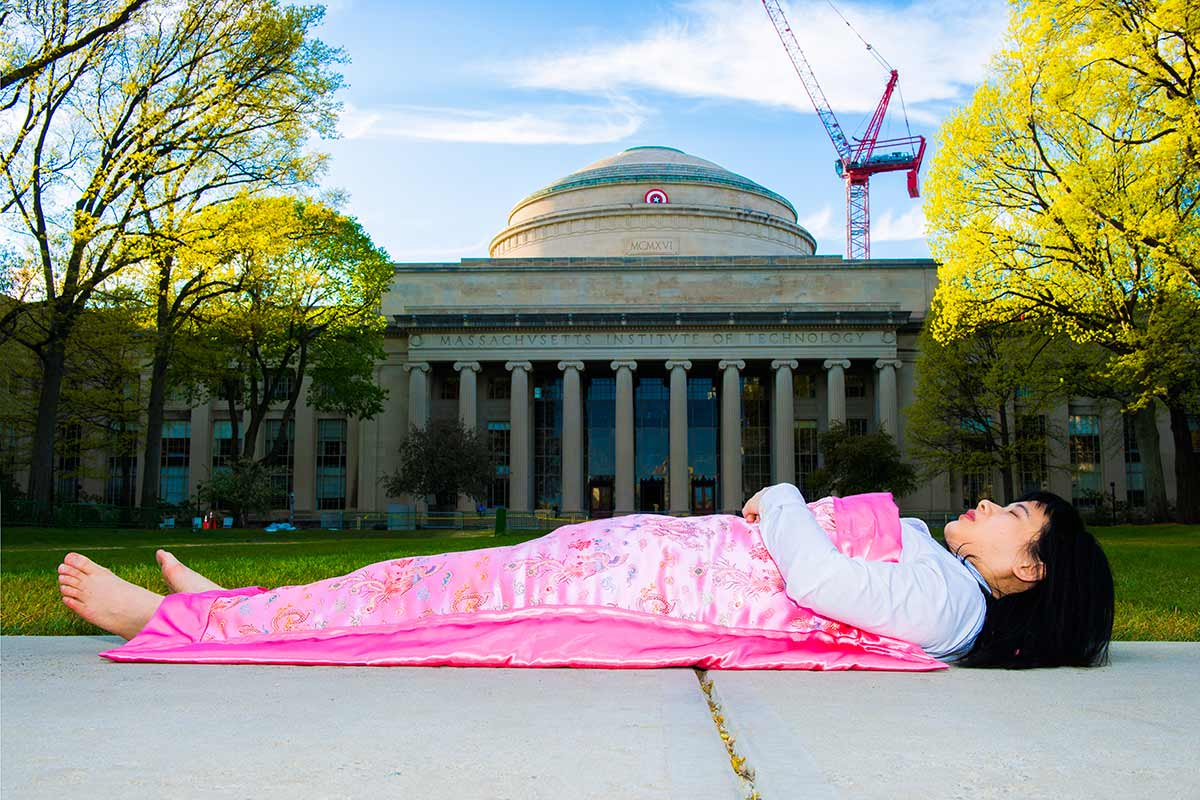 Chun Hua Catherine Dong takes photographs of herself lying in front of historical and tourist sites, covered with Chinese silk duvet
