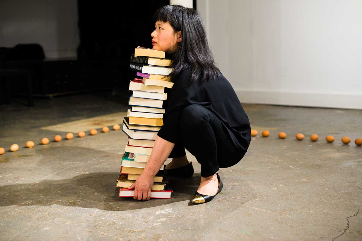 Chun Hua Catherine Dong tires to lift a stack of heavy books while being surrounded by egges