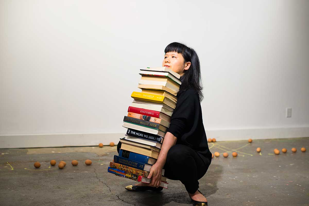 Chun Hua Catherine Dong tries to lift a stack of heavy books