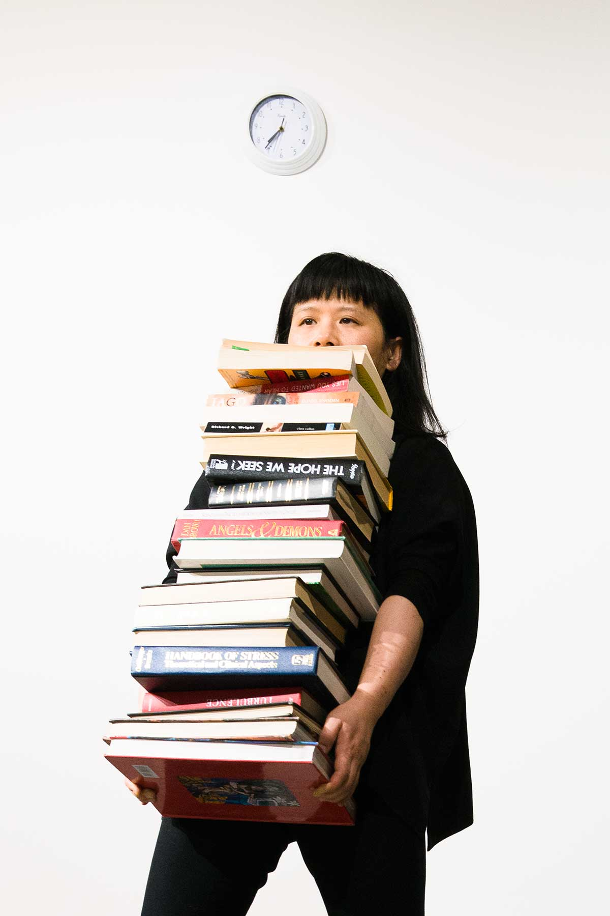 Chun Hua Catherine Dong lift a stack of heavy books and holds them as long as she can