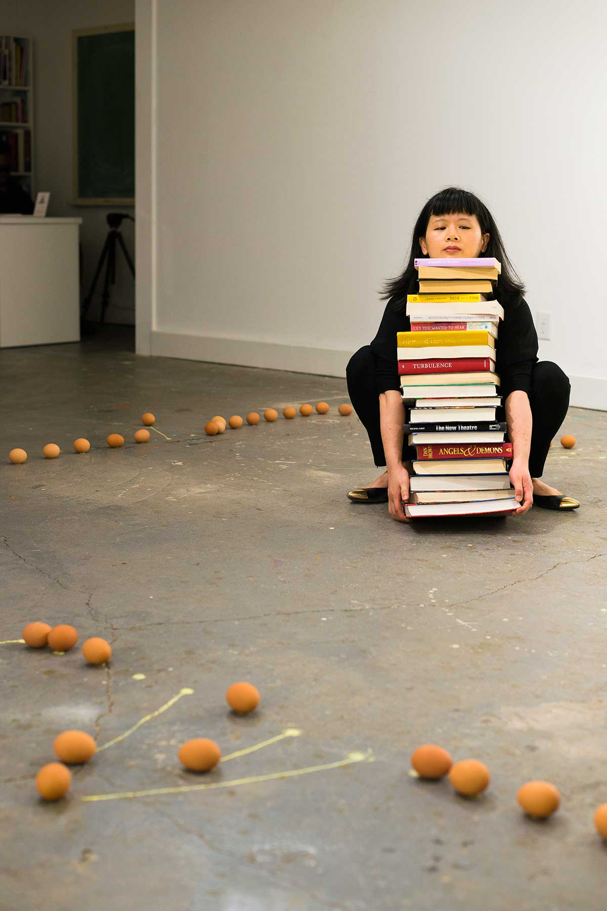 Chun Hua Catherine Dong tries to lift a stack of heavy books while being surrounded by eggs