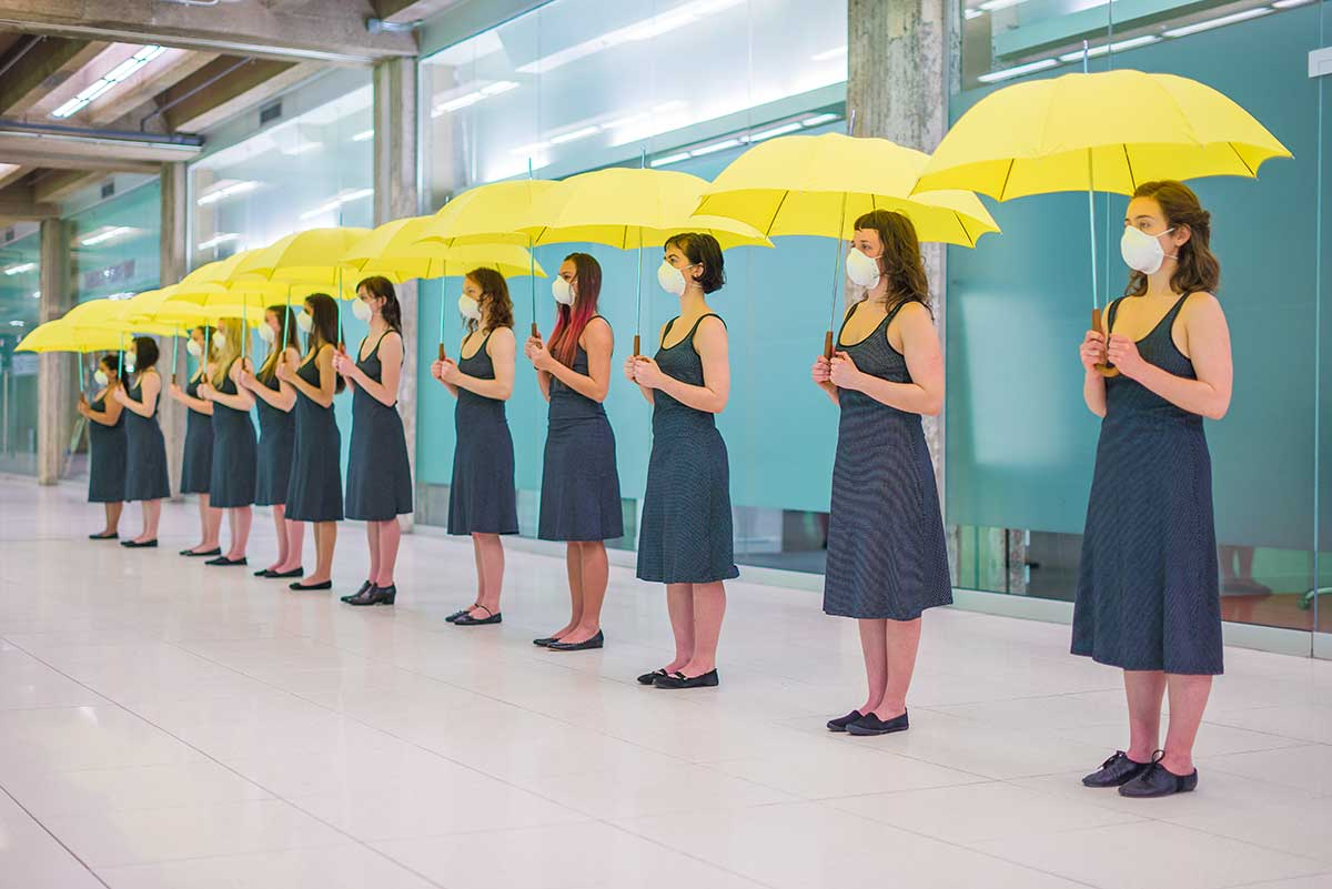 Chun Hua Catherine Dong's Yellow Umbrella performance: 12 females hold yellow umbrellas and stand still