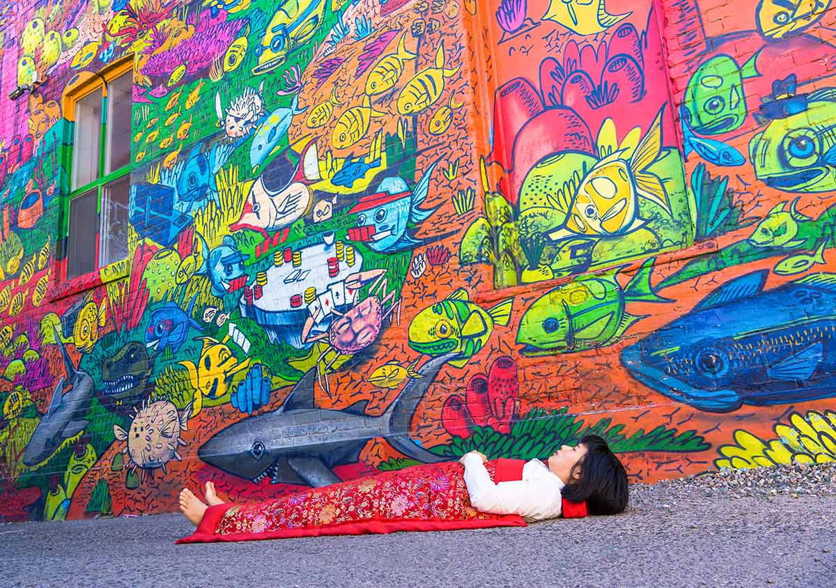 Each time Chun Hua Catherine Dong travels to a new city, she takes photographs of herself lying in front of historical cites or tourist attractions, covered with a duvet.