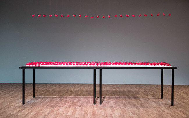 Chun Hua Catherine Dong's performance at 7a11d International Festival of Performance Art in 2016: Dong sets red paper boats and salt on a black table