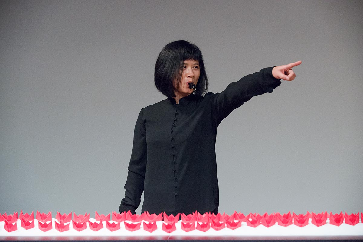 Chun Hua Catherine Dong's performance at 7a11d International Festival of Performance Art in 2016: Dong points to audiences and have a whistle in her mouth.