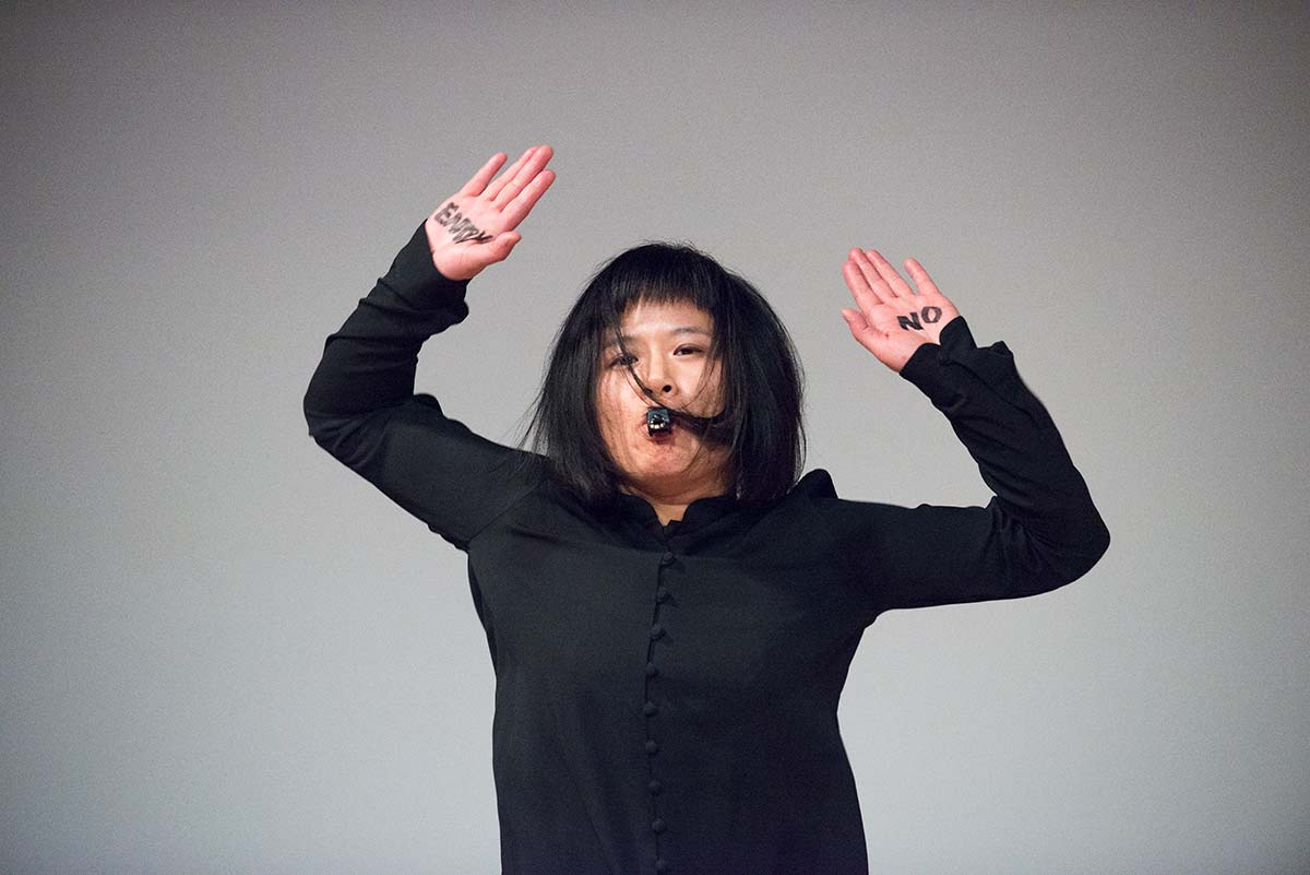 Chun Hua Catherine Dong's performance at 7a11d International Festival of Performance Art in 2016: Dong has words NO ENTRY on her hands