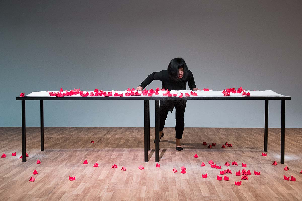 Chun Hua Catherine Dong's performance at 7a11d International Festival of Performance Art in 2016: Dong blows red paper boats to the floor