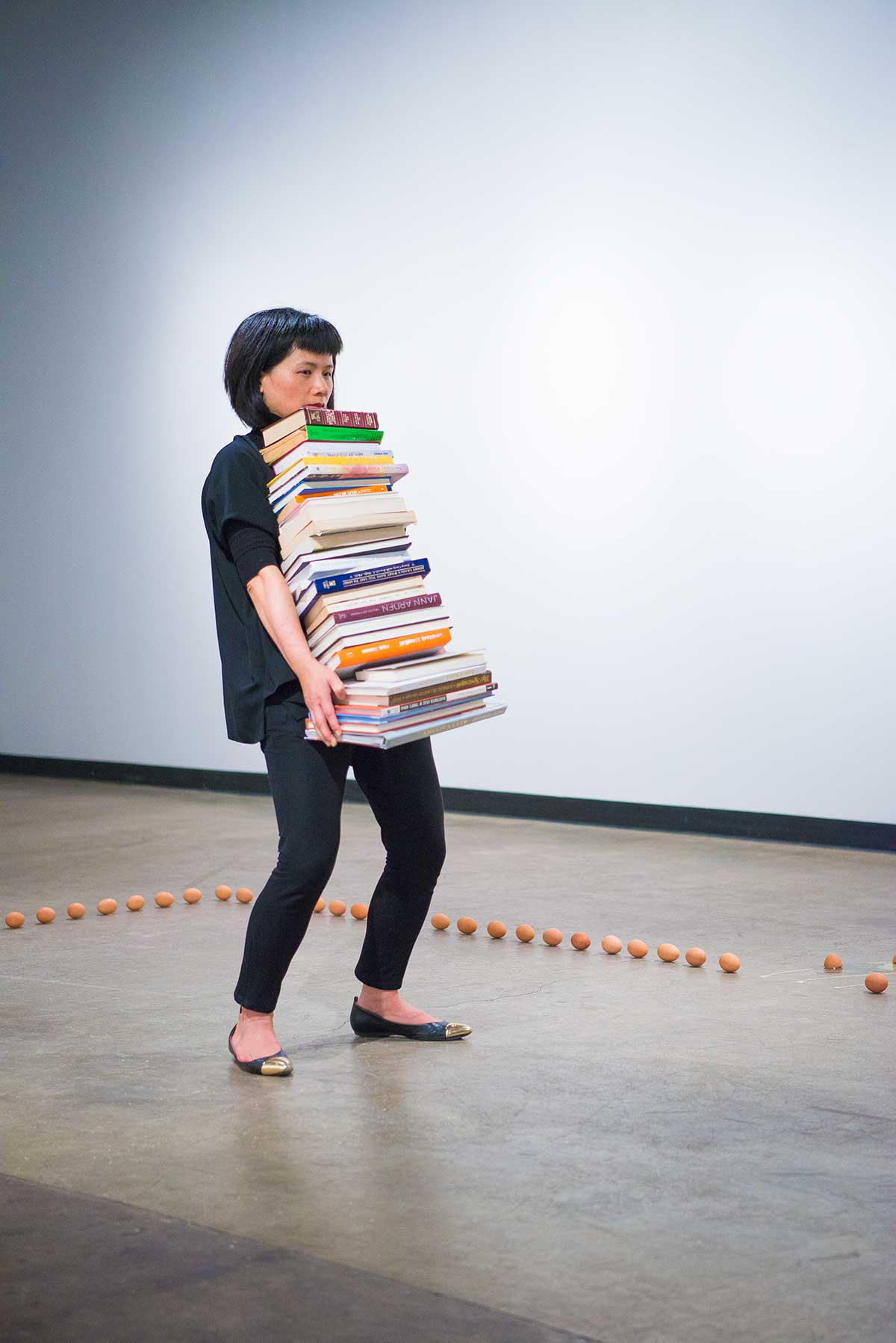 Chun Hua Catherine Dong holds a stack of books and keeps holding position as long as she can